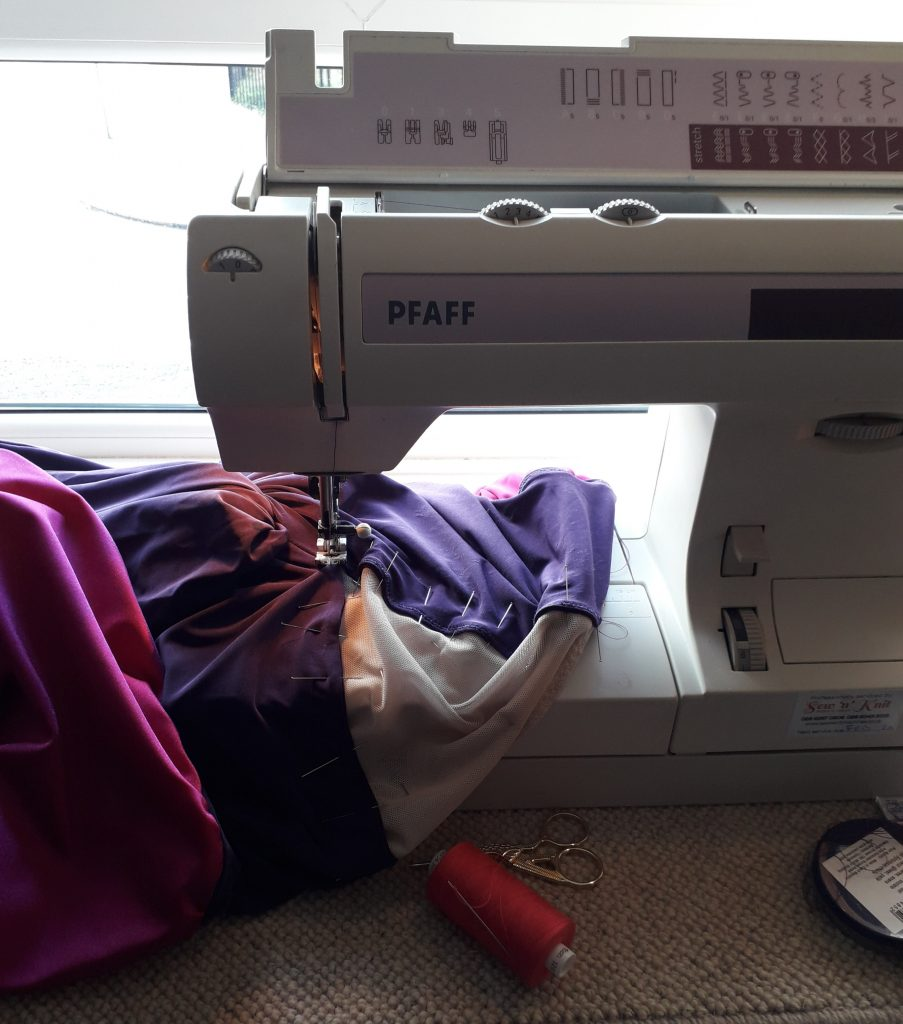 Pictured: Action shot of Claire's sewing machine working on Titania's costume. Photo is of a white sewing machine with pink, purple and white fabric under the needle. In front of the machine is a small pair of sewing scissors and a spool of bright pink thread.