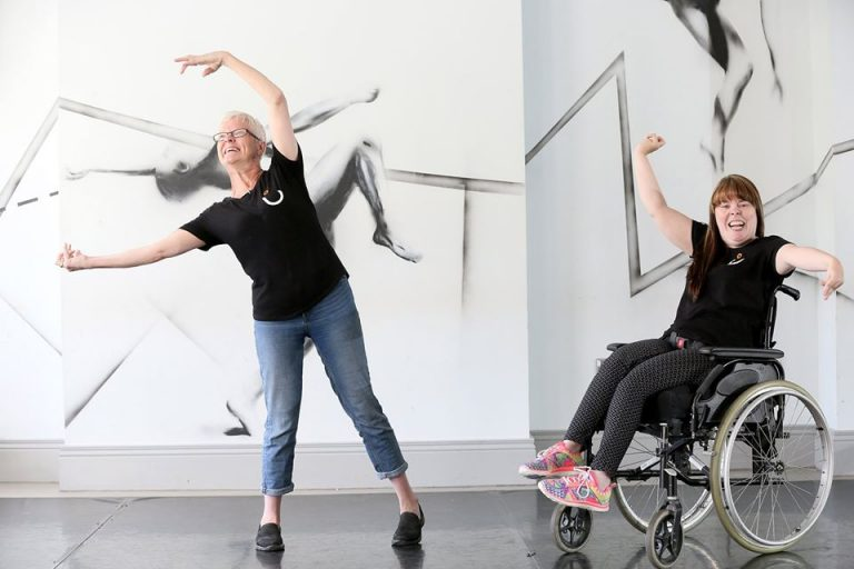 Two female dancers, one a wheelchair user pose with their arms in the air. Both are wearing black t-shirts.