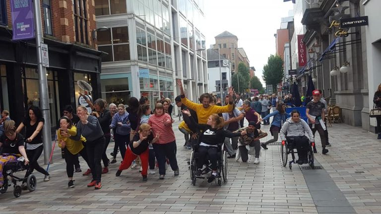 Flash mob of dancers in the middle of a main street in Belfast City Centre with onlookers. Part of the Meet Share Dance Festival weekend.