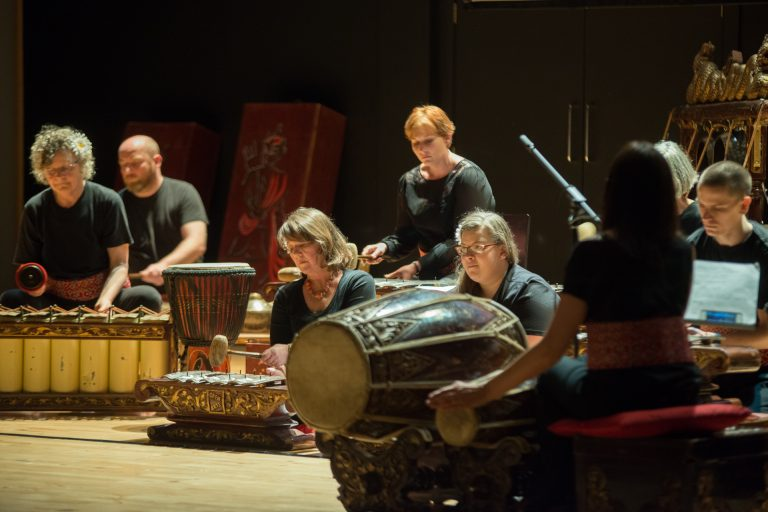 Seven gamelan members play instruments on stage at Julan Julan production whilest being conducted.
