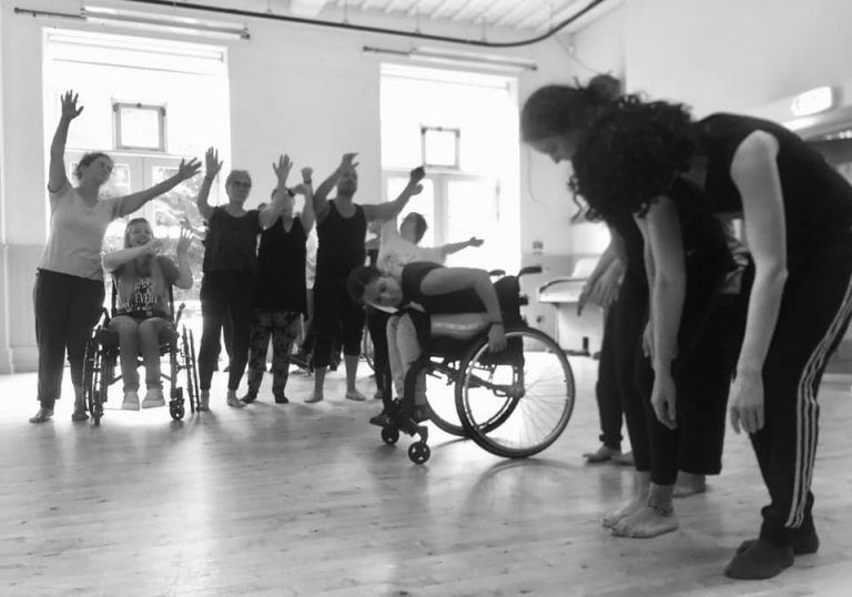 A bright room with a wooden floor and large windows. In the centre is a woman doubled over in her wheelchair with her arms stretched back holding on to the wheels. To the right of her are three females hunched up close together with their arms dangling by their sides. To the right of the central woman is a line of dancers male and female standing with their arms in the air like they are waving them from side to side.