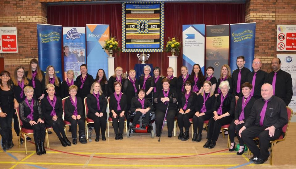 At Bangor Choral Festival 2018, the choir are in an arc shape with the front row seated and the back row standing.