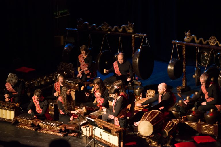 Full Gamelan orchestra on stage with performers.