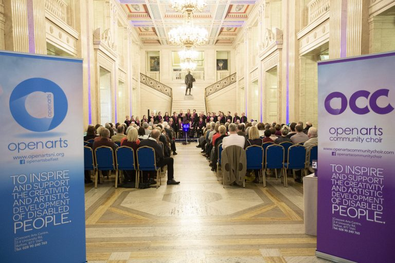 Two popup stands are in the fore front of the picture. Open Arts on the left and Open Arts Community Choir on the right. In the background is the audience that attended Choir perform in the main hall in Stormont there is a walkway in the centre of the audience.