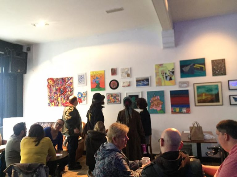 Launch of Three in One exhibition at Black Box, Belfast. Attendees mingle with one another and are staring at the artwork hung on the walls.
